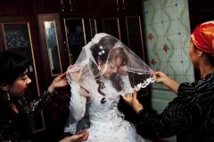 Bästa väninnan hjälper Gulmira med brudslöjan. Foto: Johan Bävman